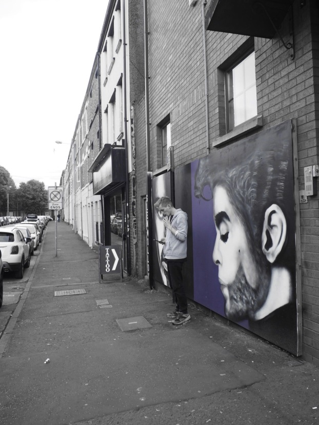 A student smoking in front of a tattoo shop- and prince mural.
